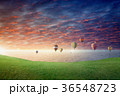 Hot air balloons fly in glowing sunset sky  36548723