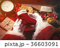 Santa Claus wrapping up Christmas gifts  36603091