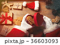 Santa Claus wrapping up Christmas gifts  36603093