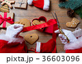 Santa Claus wrapping up Christmas gifts  36603096
