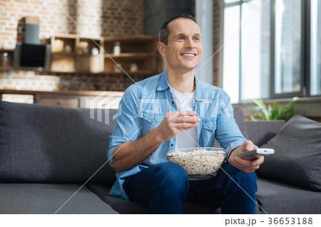 Happy young man watching interesting program 36653188