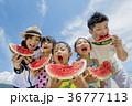 夏の海辺でスイカを食べる5人家族 36777113