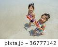 夏の海辺をスイカを持って歩く姉妹 36777142