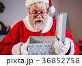 Santa claus opening a gift box 36852758