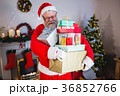 Santa claus holding a stack of gifts at home 36852766