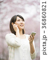 桜の前で音楽を聴く女性 36860821