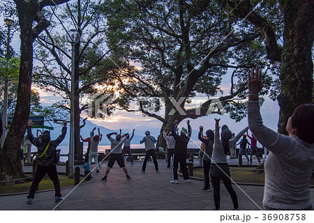 鹿児島 早朝の桜島と錦江湾を眺めながらラジオ体操をする人々 36908758