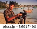 Guy Photographer Looks at Camera on Sea Beach 36917498