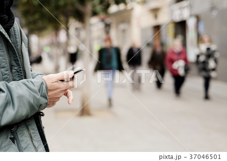 young man using a smartphone in the street 37046501
