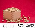 枡から溢れる節分の福豆 紅色の和紙の背景 b-2  左寄せ やや横から 37218052