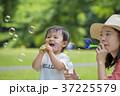 新緑の公園でシャボン玉を吹く母と息子 37225579