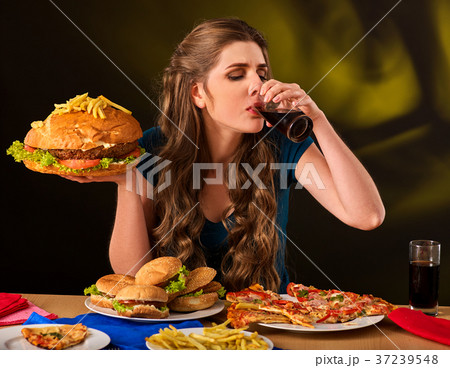 Woman eating french fries and hamburger on table. 37239548