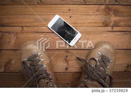 画面が割れたスマートフォンを踏む足 37259829