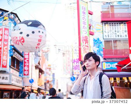 大阪観光 スマホで通話する一人旅の男性 37307452