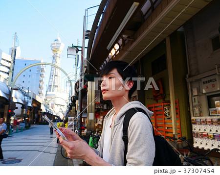 大阪観光 地図を確認する一人旅の男性 37307454