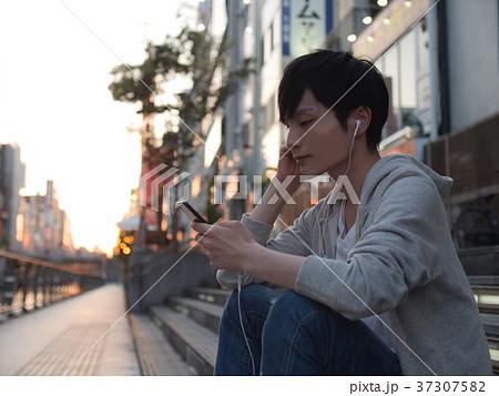 スマホで音楽を聴く男性 37307582