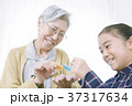 折り紙を折るおばあちゃんと女の子 37317634