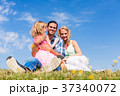 Family sitting in green grass on meadow 37340072