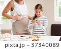 Pregnant mum and her little daughter baking 37340089