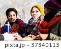 Young friends talking at picnic outdoors in the 37340113
