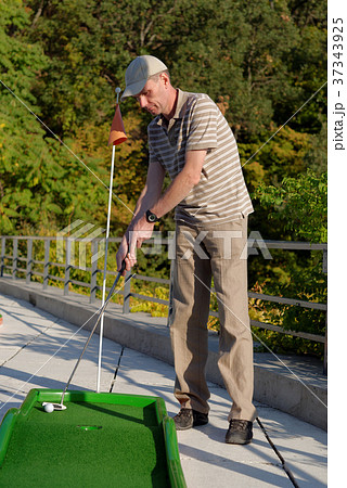 Man plays minigolf 37343925