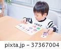 ダイニングテーブルで国旗のパズルで遊ぶ幼児 37367004