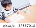 ダイニングテーブルで国旗のパズルで遊ぶ幼児 37367018