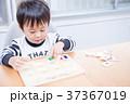 ダイニングテーブルで国旗のパズルで遊ぶ幼児 37367019