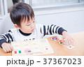 ダイニングテーブルで国旗のパズルで遊ぶ幼児 37367023