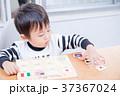ダイニングテーブルで国旗のパズルで遊ぶ幼児 37367024