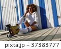 Young black woman on roller skates sitting near a beach hut. 37383777