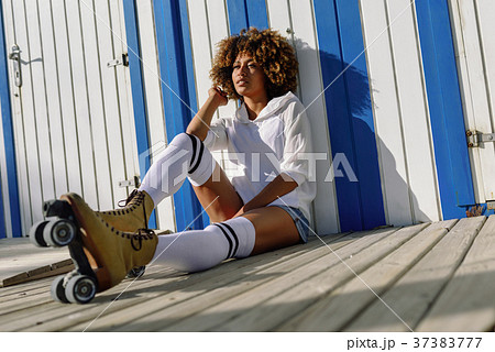 Young black woman on roller skates sitting near a beach hut. 37383777