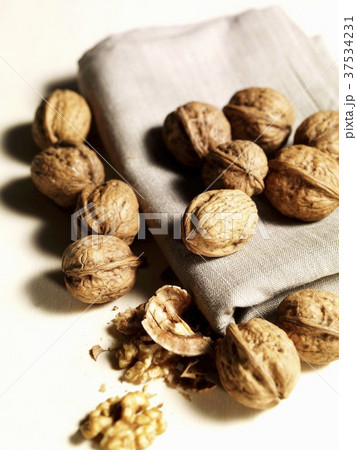 Shelled and unshelled walnuts on cloth 37534231