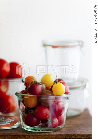 Multi-Colored Cherry Tomatoes in a Glass Container 37540076
