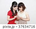 スマホとワンピースを着た二人の若い女性 37634716