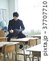 教室にいるグローブをした男子学生 37707710
