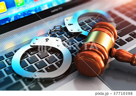Handcuffs and judge mallet on laptop keyboard 37710398