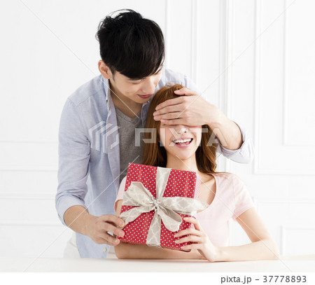 man surprises his girlfriend with present at homeの写真素材