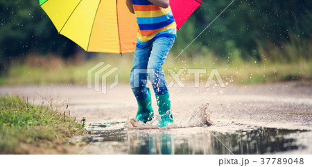 Child walking in wellies in puddle on rainy 37789048