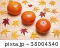 木のテーブルの上の柿と紅葉したカエデの葉 38004340