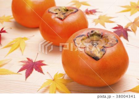 木のテーブルの上の柿と紅葉したカエデの葉 38004341