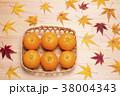 木のテーブルの上の笊に入ったミカンと紅葉したカエデの葉 38004343
