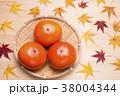 木のテーブルの上の笊に入った柿と紅葉したカエデの葉 38004344