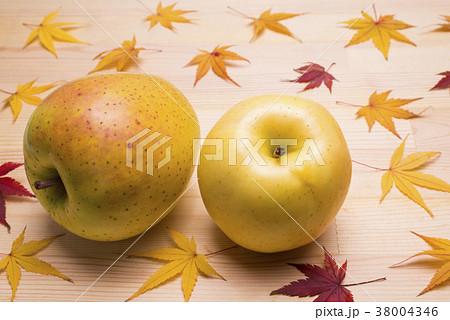 木のテーブルの上のリンゴと紅葉したカエデの葉 38004346
