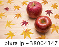 木のテーブルの上のリンゴと紅葉したカエデの葉 38004347