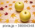 木のテーブルの上のリンゴと紅葉したカエデの葉 38004348