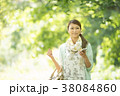 新緑の中でスマートフォンを見る女性 38084860