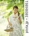 新緑の中でスマートフォンを見る女性 38084861
