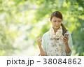 新緑の中でスマートフォンを見る女性 38084862