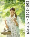 新緑の中でスマートフォンを見る女性 38084863